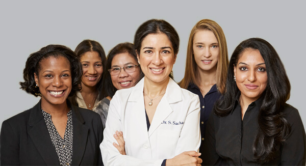 Dentist NYC - Dr. Sachar with her team of dental assistants and administrative staff all smiling at Sachar Dental